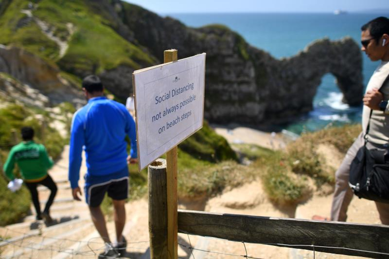 People pass a sign advising that social distancing may not be possible as they walk down a footpath towards the popular tourist spot Durdle Door near West Lulworth on the south coast of England on Sunday. (AFP photo)