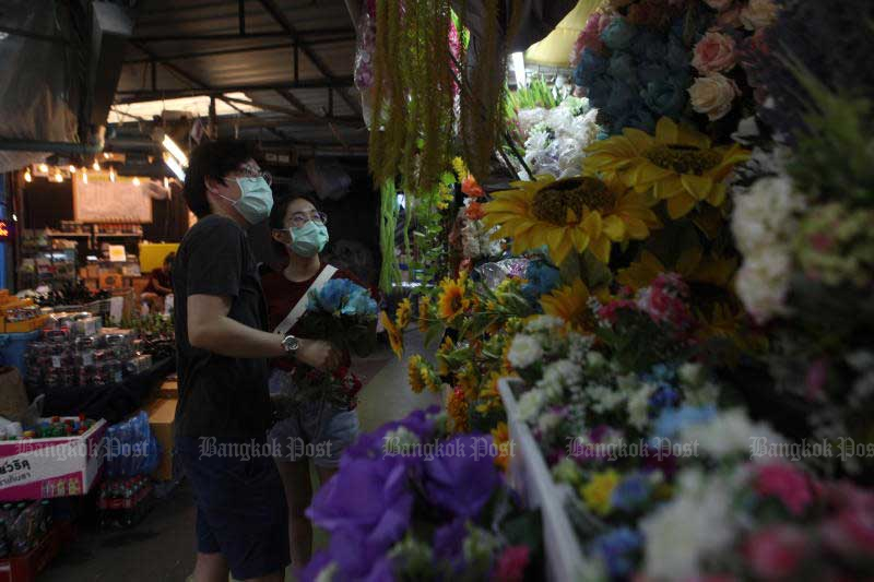 The Chatuchak Weekend Market draws shoppers on Sunday after it was allowed to reopen. The government plans to reopen more businesses next month. (Photo by Arnun Chonmahatrakool)