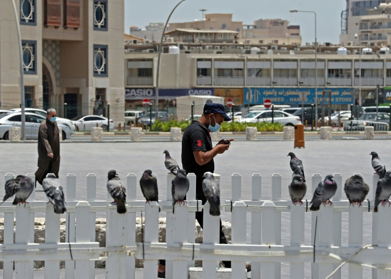 A masked man checks his phone in Qatar where residents and citizens have been required by law to install a coronavirus contact tracing app on their handsets since Friday.