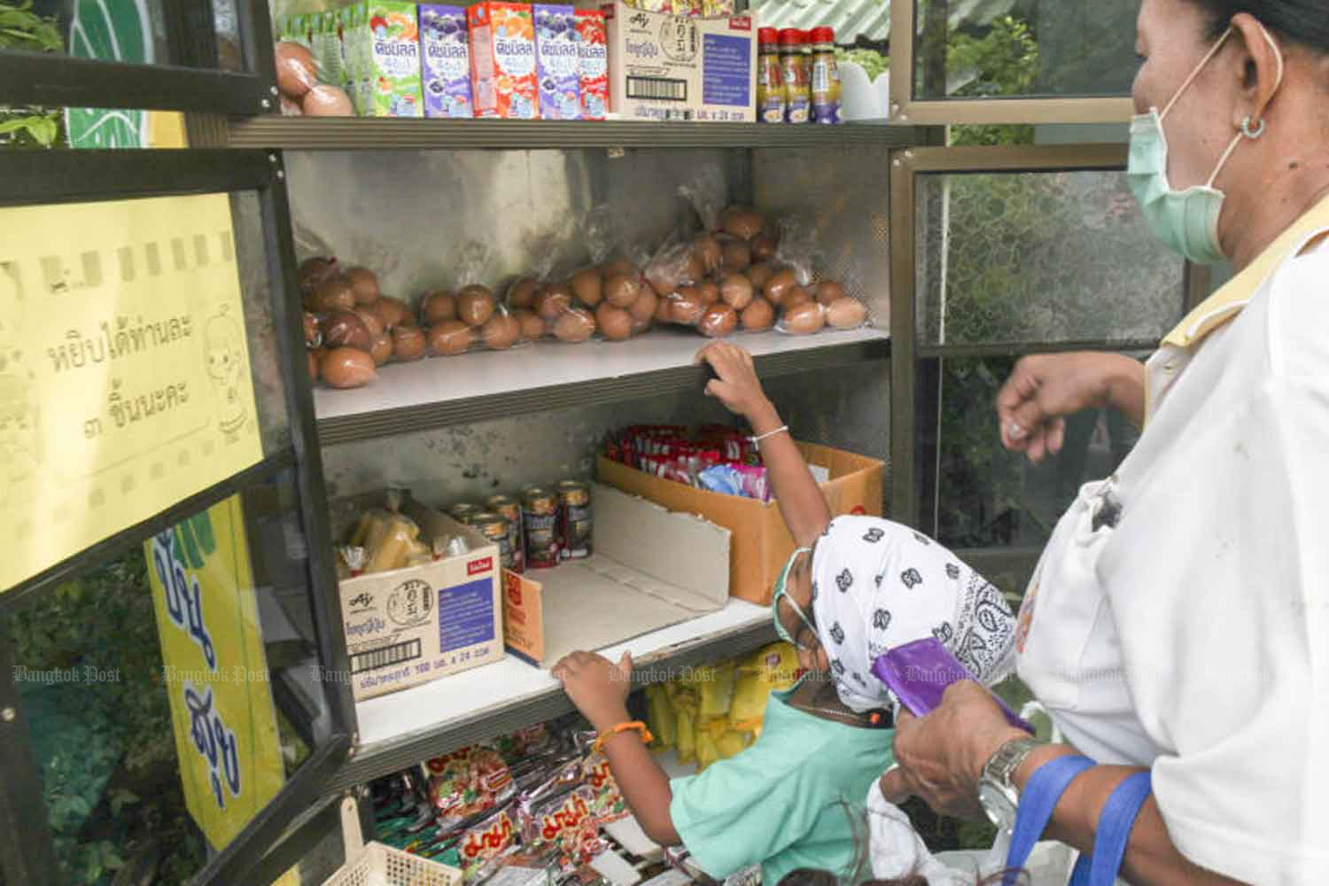 A child reaches for donated eggs in a 'tu pan suk', or a happiness-sharing pantry, in front of the Department of Agriculture in Bangkok. An instruction, apparently aimed to regulate people queuing up for donations, reads 'three items for each person, please'. Arnun Chonmahatrakool
