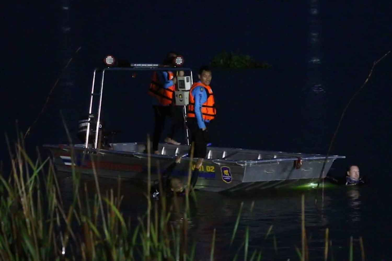 Rescuers scour Bung Thung Sang swamp in Khon Kaen's Muang district on Monday night for a man whose small flat-bottomed boat capsized during a storm on Monday. His body was later recovered. (Photo: Chakrapan Nathanri)