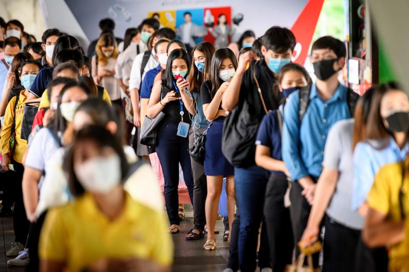 Commuters stand in line to enter a train station already filled to capacity because of social distancing rules at rush hour in Bangkok on Monday as Thais continued their return to work following the lifting of restrictions to halt the spread of the Covid-19 coronavirus. (AFP)