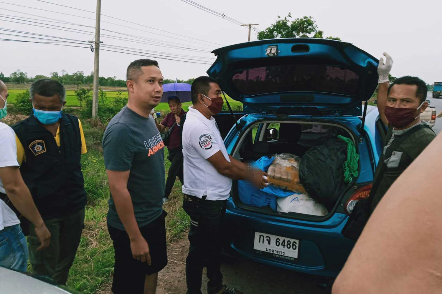 Somphan Sri-ubon, 43, in a white T-shirt, is caught with sacks containing meth pills in  his car in Kantharawichai district, Maha Sarakham province, on Monday. (Photo: Yongyuth Phuphuangpet)