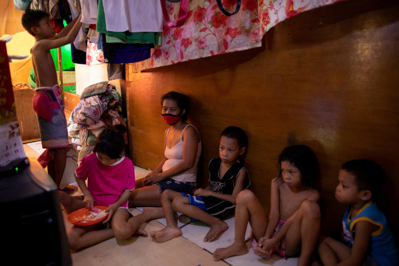 Michelle Asinto, 42, wears a mask for protection against the coronavirus disease while her children share a plate of rice with soy sauce for lunch, in their shanty home along an estuary in Manila, Philippines, May 6, 2020. (Reuters file photo)