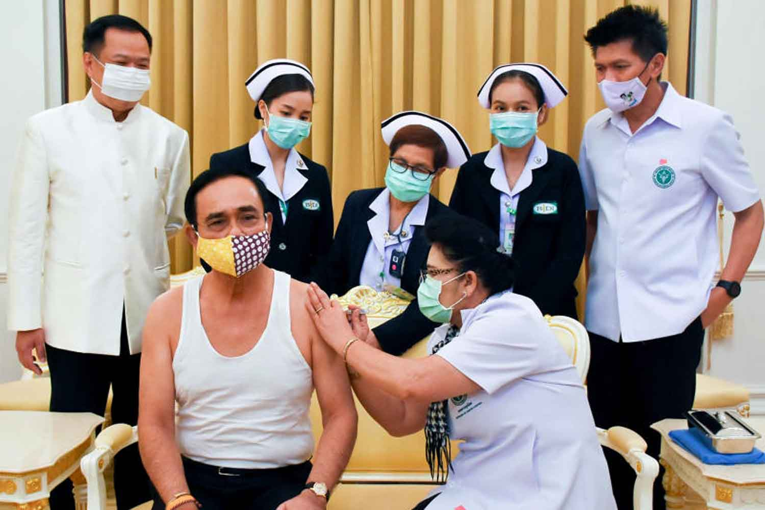 Prime Minister Prayut Chan-o-cha is given an influenza vaccine at Government House. Looking on are Public Health Minister Anutin Charnvirakul, left, and several healthcare workers. (Government House photo)