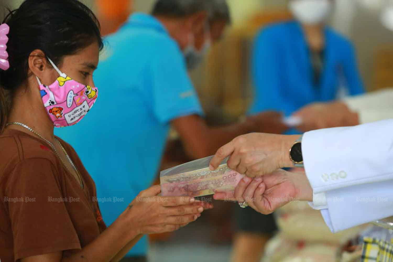 People queue up at Wat Yai Bang Phli Klang in Samut Prakan's Bang Phli district early this month to receive a cash handout of 2,000 baht and 5kg of rice donated by the privately run Chularat 3 Hospital, which is located nearby, to alleviate the economic effects of the Covid-19 pandemic. (Photo: Somchai Poomlard)