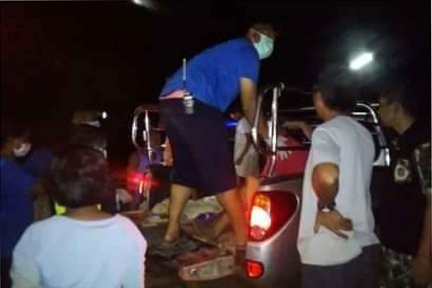 One of the two Myanmar men injured by a wild elephant in Kanchanaburi is helped into a pickup before being taken to hospital. (Photo: Piyarat Chongcharoen)