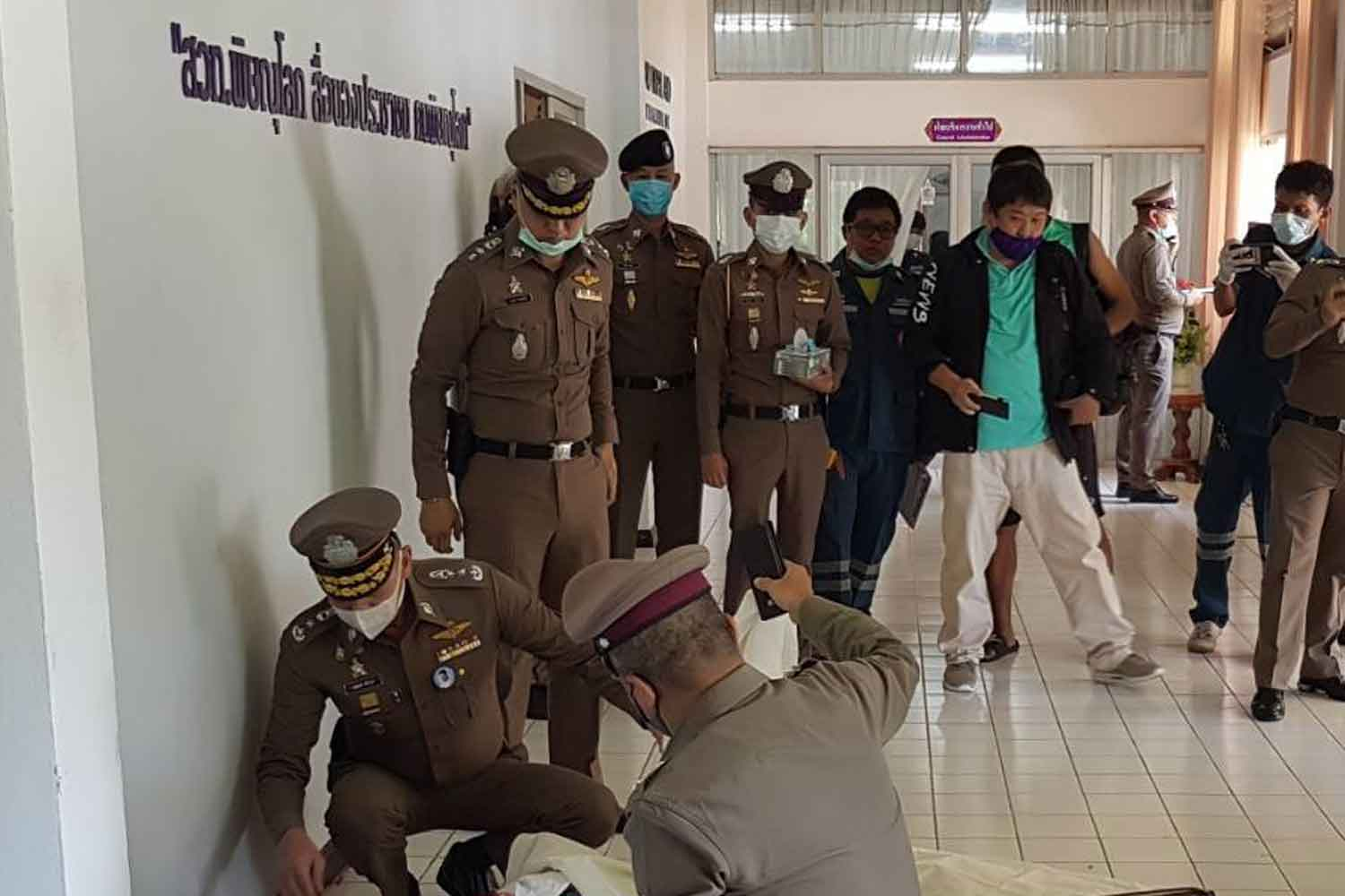 Police cover the body of one of the victims of a the shooting spree at the Radio Thailand station in Phitsanulok. Three people, including the station director, were killed, and a fourth wounded. (Photo by Chinnawat Singha)