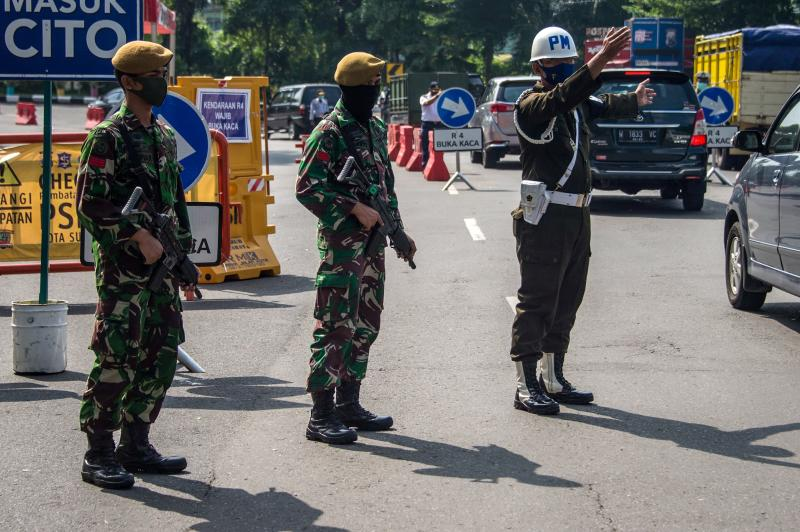 Indonesian troops man a Covid-19 checkpoint in Surabaya, East Java on Wednesday. (AFP photo)
