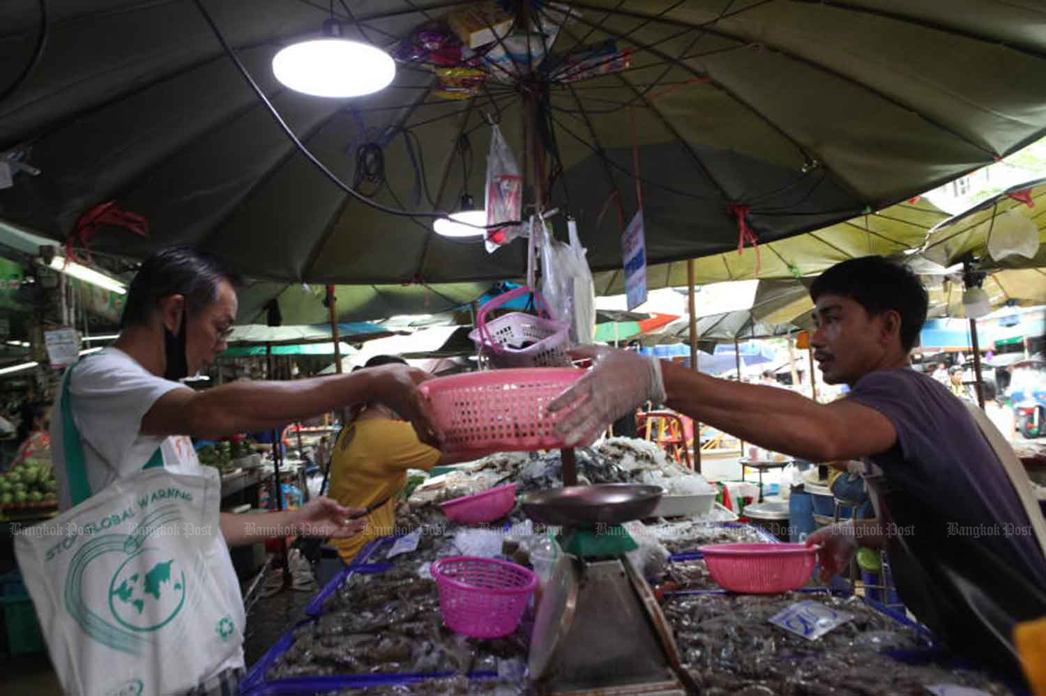 Some vendors and customers remove face masks at Wong Wian Yai market in Bangkok on Thursday even though the government is asking people to wear them. Security officials say all businesses and activities will be allowed to resume in July. (Photo by Arnun Chonmahatrakool)
