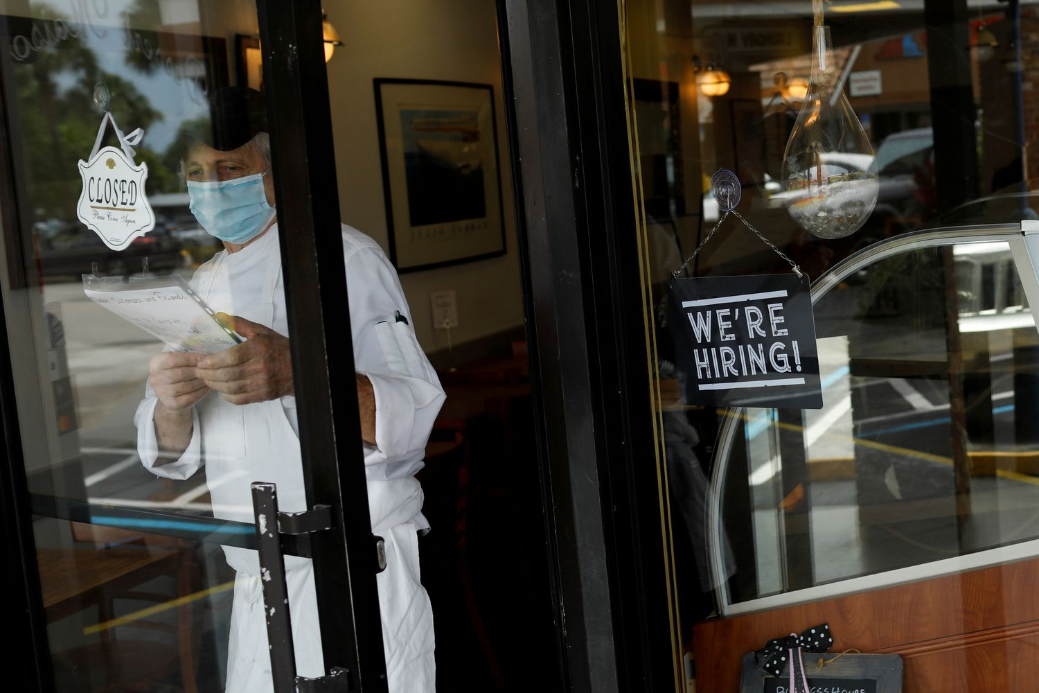 A 'We're Hiring' sign advertising jobs is seen at the entrance of a restaurant, as Miami-Dade County eases some of the lockdown measures put in place during the coronavirus disease outbreak, in Miami, Florida, on May 18. (Reuters photo)
