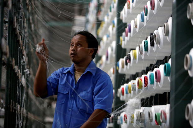 A quality control worker examines yarn at PT Trisula International in Bandung, West Java province, on Sept 17, 2013. (Photo: Reuters)