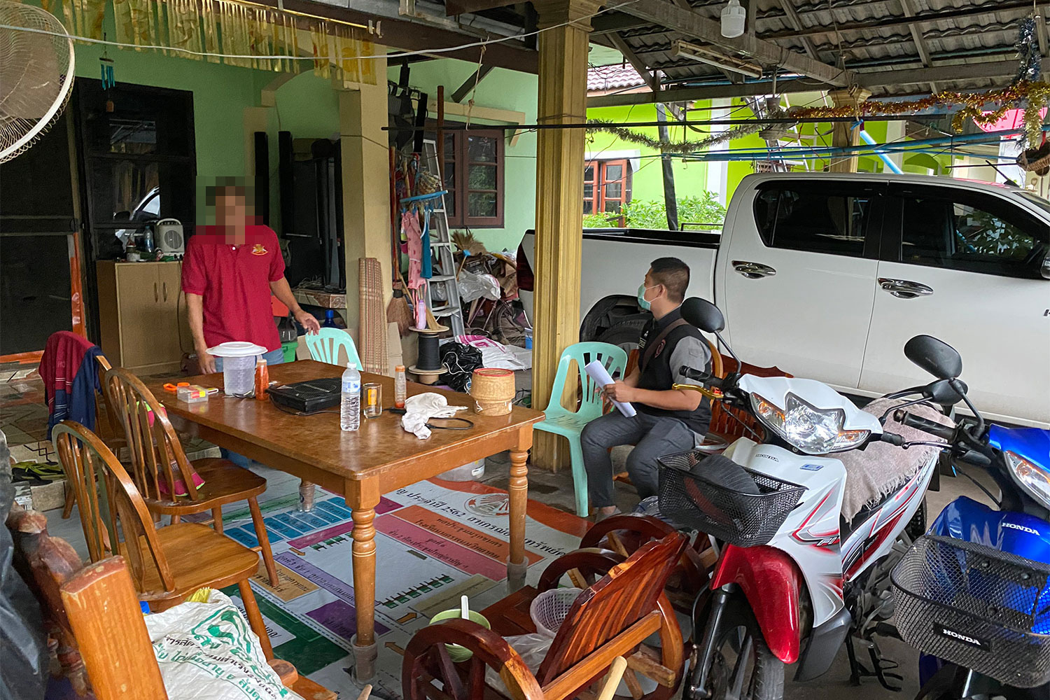 A police officer serves an arrest warrant on the accused teacher at a house in Muang district of Nakhon Phanom province on Friday. (Photo: Pattanapong Sripiachai)