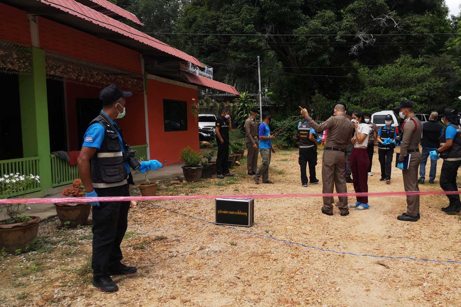 Police cordon off the house in Kantang district of Trang on Friday after a suspect in a murder in Phatthalung last year shot himself dead rather than face arrest. (Photo: Methee Muangkaew)