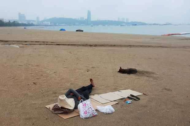 A man sleeps on an almost empty beach in Pattaya, which is usually crowded with tourists, on April 26. (Reuters photo)