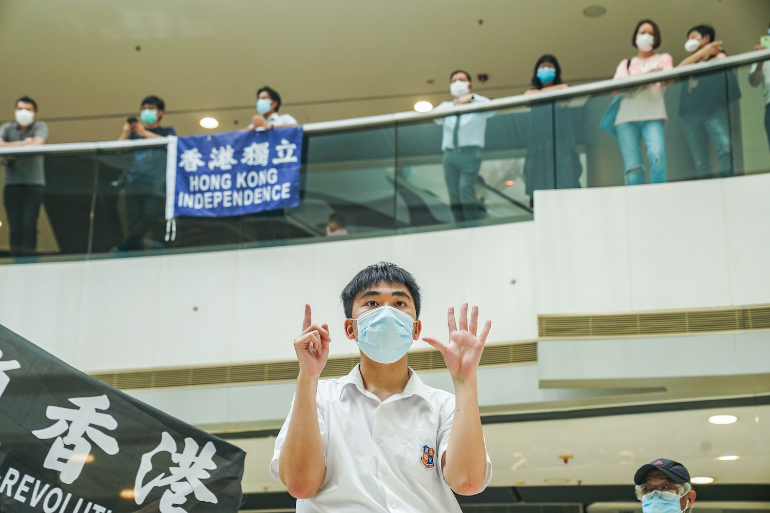 """A student makes a gesture indicating """"Five demands, not one less"""", one of the mottos of pro-democracy activists, during a lunchtime protest at the International Finance Center (IFC) shopping mall in Hong Kong on Friday. (Bloomberg Photo)"""