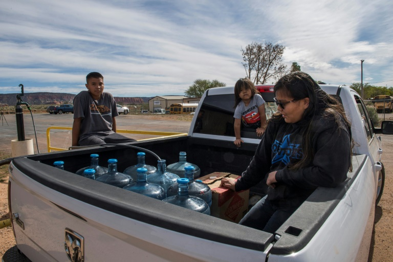 Members of the Larson family who have no running water in their home, collect water from a distribution point in the Navajo Nation town of Thoreau.