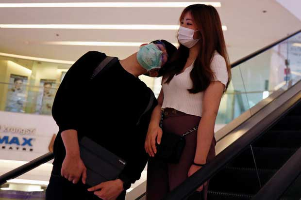 A couple wearing protective face masks is pictured on the escalator inside a shopping mall on Friday, after the government eased isolation measures. (Reuters photo)