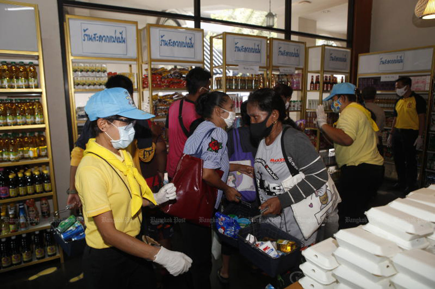 People take free food, drinks and everyday items at a sharing store on Ekkamai Soi 3 in Bangkok's Watthana district on Friday. Each was allowed to take five items. The store is open from 11am to 1pm and from 3pm to 5pm each day until June 26 to help people affected by the impact of the Covid-19 outbreak. (Photo: Nutthawat Wicheanbut)