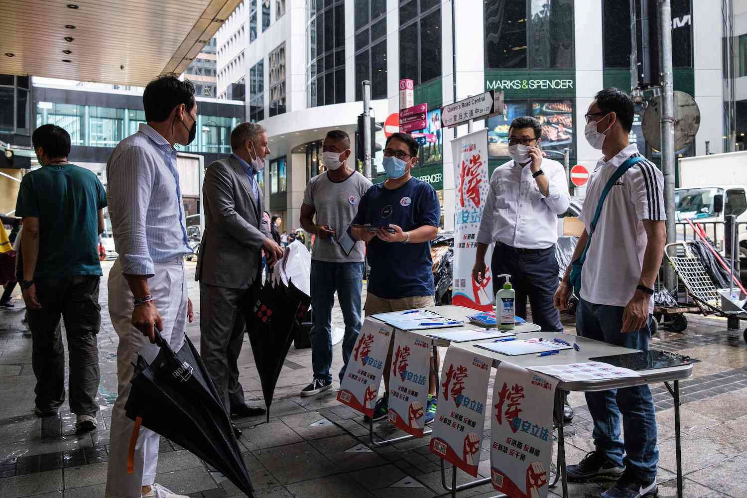 Pedestrians stop at a booth set up by a pro-China group on Friday to gather signatures in support of a new security law in Hong Kong. (AFP Photo)