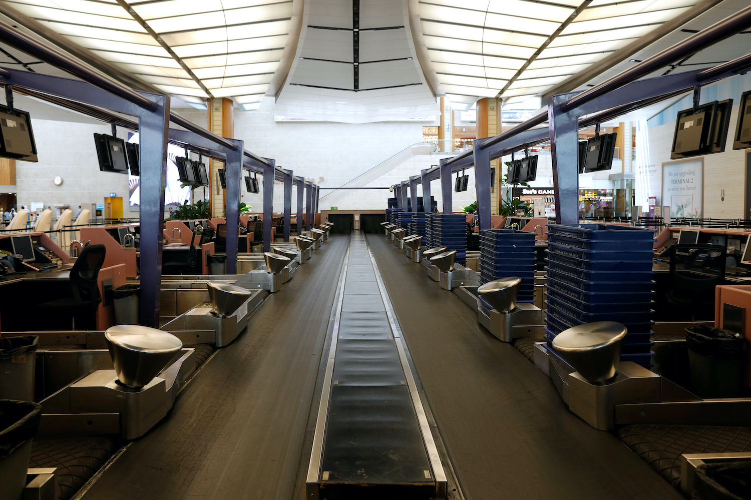 A baggage conveyor belt runs between rows of empty check-in counters at Changi Airport in Singapore. (Reuters Photo)