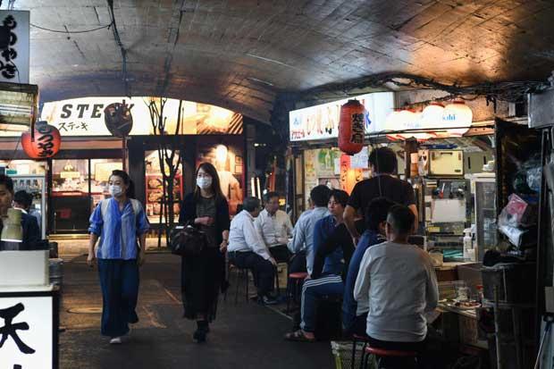 Pedestrians wearing protective masks walk past Izakaya bars in Yurakucho district of Tokyo on Friday. (Bloomberg photo)