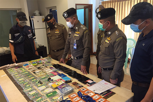 Immigration police show the evidence seized from a raid at an online gambling den in Mae Sot district of Tak province on Saturday. (Photo by Wassayos Ngamkham)