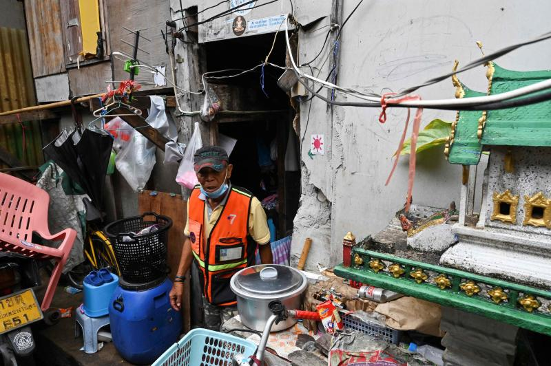 A motorcycle taxi driver leaves his home in Bangkok on Saturday. (AFP photo)