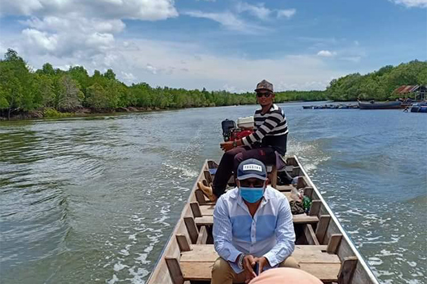 Chebilang mayor Mahmadneesum Bilungload rides a long-tailed boat from Chebilang canal to the Andaman Sea in Muang district of Satun province on Saturday to track the escape route of an shark that bit a boy's foot. (Photo from Chebilang Municipality Facebook account).