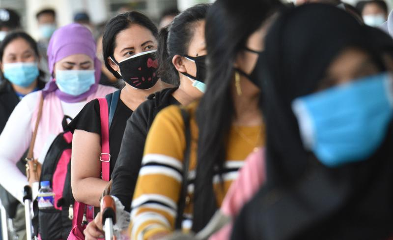 Philippine overseas workers who were quarantined for weeks after returning home queue up in the departures area as they wait for flights back to their home cities around the country, at Manila's international airport on May 28, 2020. (AFP)