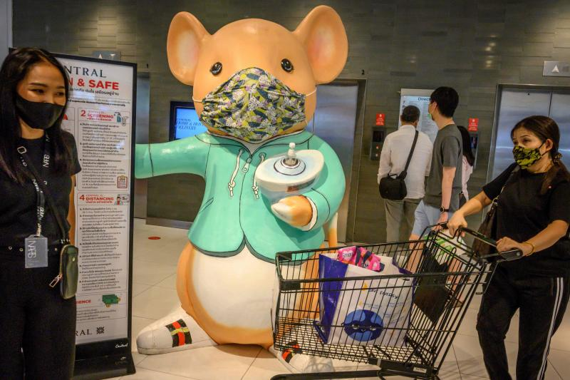 People walk in front of a giant mouse distributing hand sanitiser in a shopping mall in Bangkok on Sunday. (AFP photo)