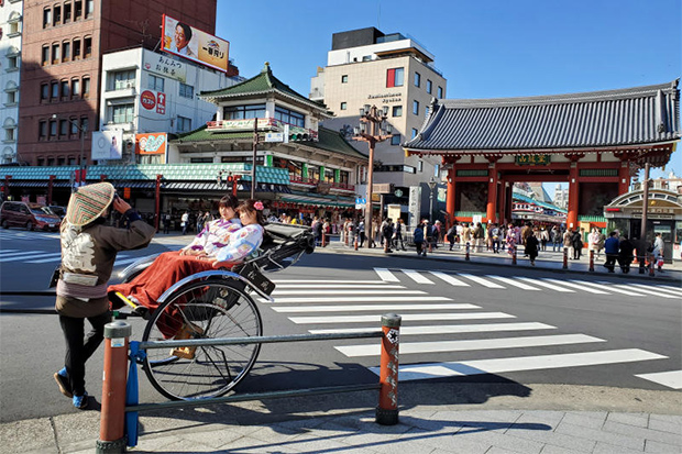 A rickshaw driver takes a souvenir photo for his clients in Asakusa district of Tokyo on March 25. (Photo: Reuters)