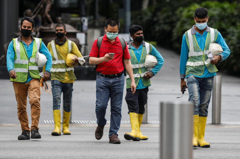 Migrant workers in essential services wearing safety vests cross a street at Orchard Road, amid the coronavirus disease (Covid-19) outbreak in Singapore, May 27, 2020. (Reuters photo)