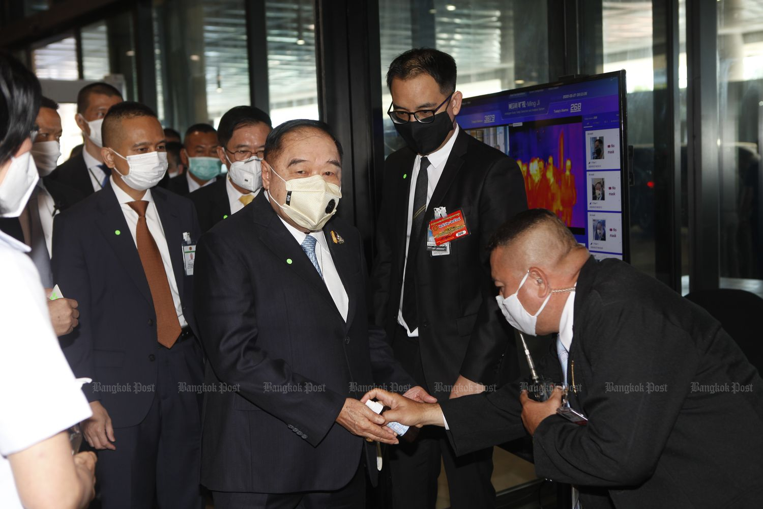 Deputy Prime Minister Gen Prawit Wongsuwon, who is also chief strategist of Palang Pracharath party, has his hands cleaned as he arrives at Parliament on Wednesday to hear the debate on the Covid-19 decrees proposed by the government. (Photo by Nutthawat Wichieanbut)