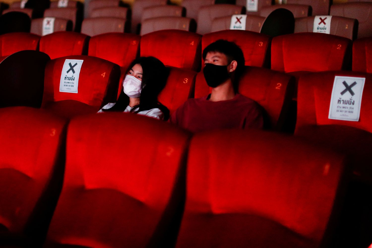 People wearing protective face masks are seen inside a movie theatre during its reopening after the government eased isolation measures to prevent the spread of the coronavirus disease in Bangkok on Monday. (Reuters photo)