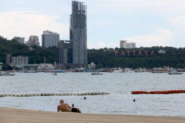 A tourist relaxes on a beach in Pattaya after the resort city reopens all beaches for visitors on Monday. (Photo byWichan Charoenkiatpakul)