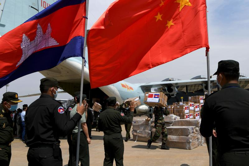 Cambodian soldiers carry aid including medical equipment from China's Ministry of Defence, to be used to combat the spread of the  coronavirus, as others look on with national flags, at Phnom Penh International Airport in Phnom Penh on April 25, 2020. (AFP photo)