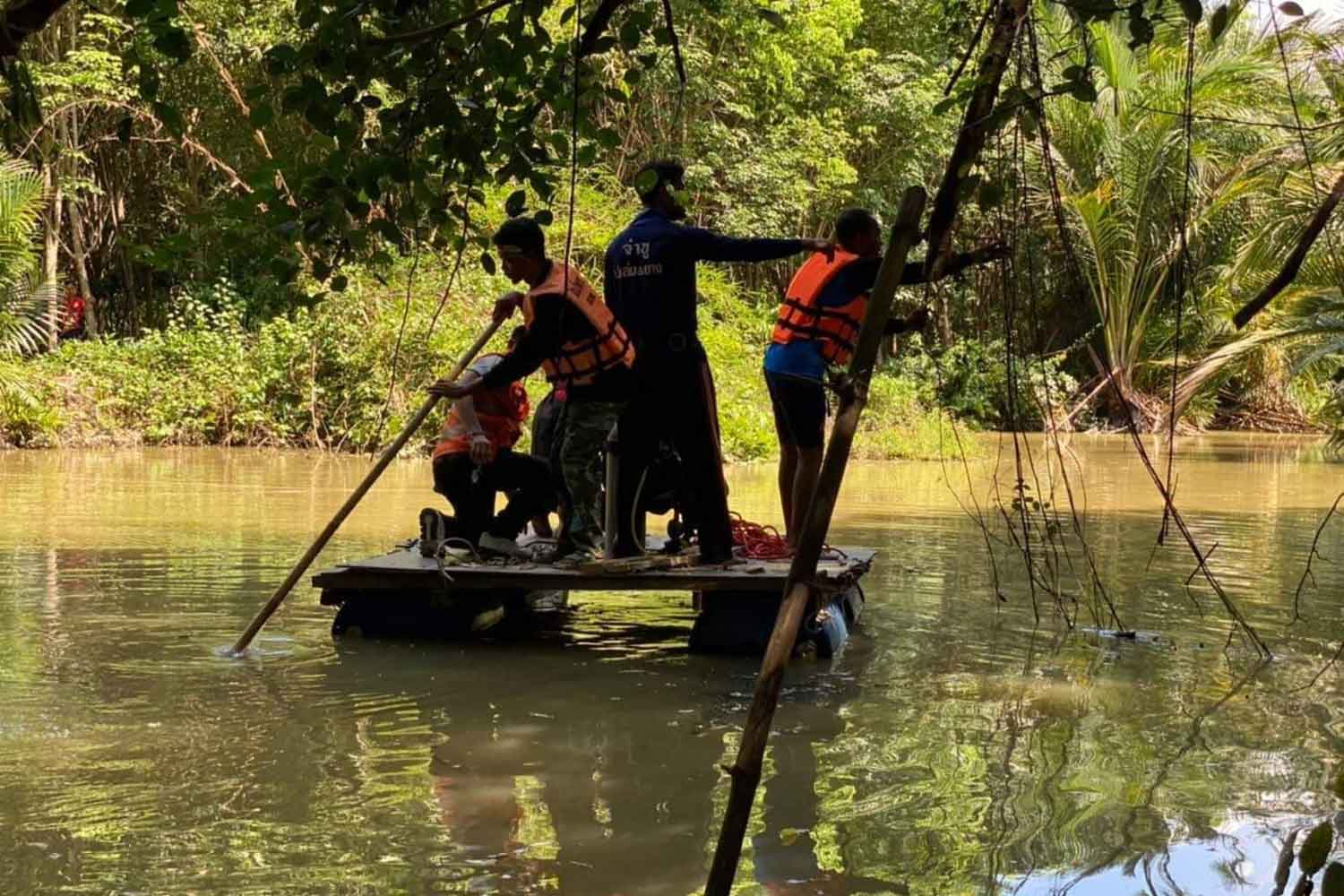 Rescuers on a raft search a canal in Sichon district, Nakhon Si Thammarat, for a man who disappeared while fishing, and later found his body. (Photo: Nujaree Raekrun)