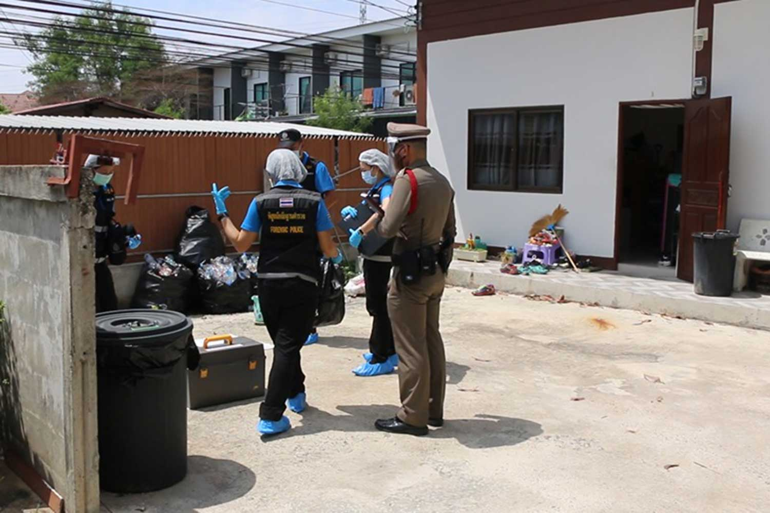 A police officer and forensic investigators in the yard of the rented premises in Khon Kaen where a young man was found stabbed to death on May 28. (File photo by Chakkraphan Natanri)
