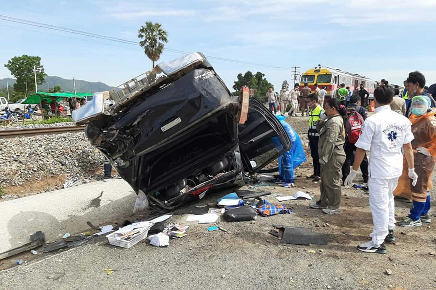 Police and rescue workers with the wreckage of the pickup truck hit by a passenger train at a crossing in Phayuha Khiri district of Nakhon Sawan on Tuesday morning. The driver, a village head, was killed. (Photo: Chalit Pumruang)