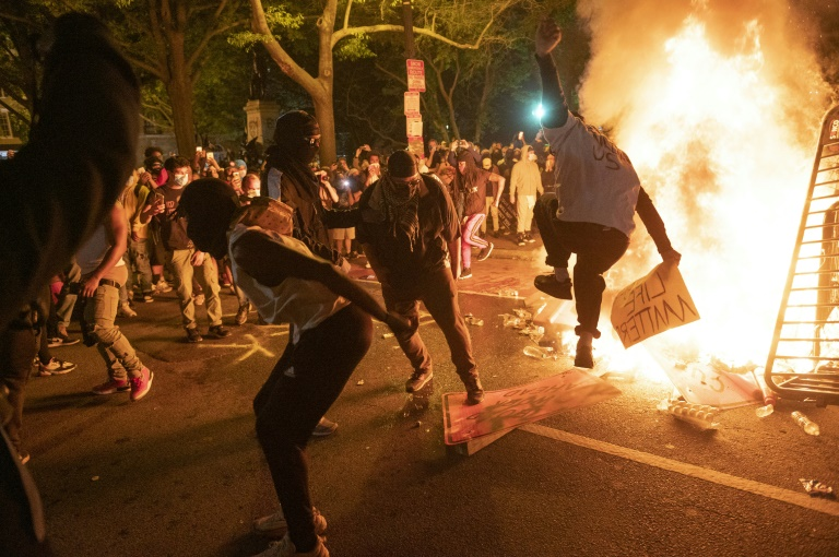 Protesters jump on a street sign near a burning barricade during a demonstration against the death of George Floyd near the White House on May 31, 2020.