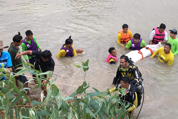 Divers extract the body of a 12-year-old boy from a pond in Chum Phuang district of Nakhon Ratchasima on Tuesday. (Photo by Prasit Tangprasert)