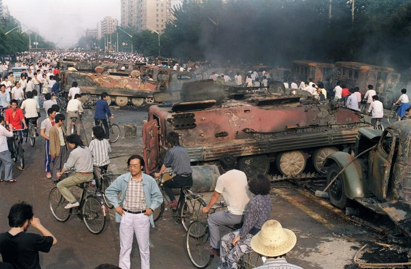 In this file photo taken on June 4, 1989, residents gather near the smoking remains of over 20 armoured personnel carriers burnt by demonstrators during clashes with soldiers near Tiananmen Square in Beijing. (AFP)