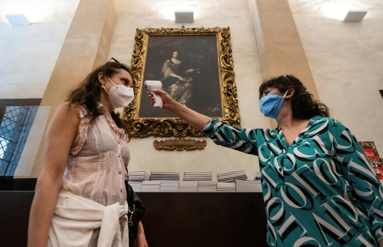 A journalist gets her temperature checked at the Uffizi Gallery Museum in Florence.