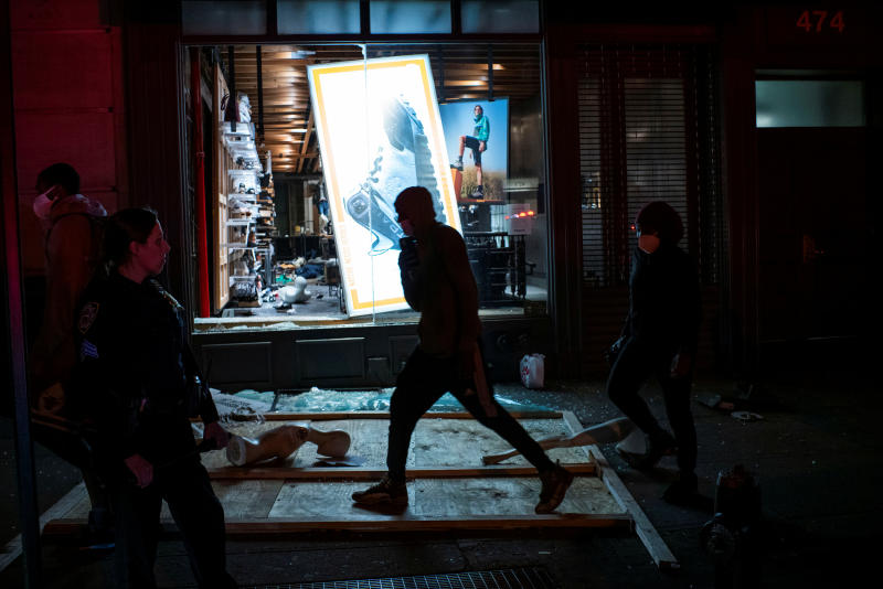 Protesters pass by a store looted after a march against the death in Minneapolis police custody of George Floyd, in the Manhattan borough of New York City on Tuesday. (Reuters photo)