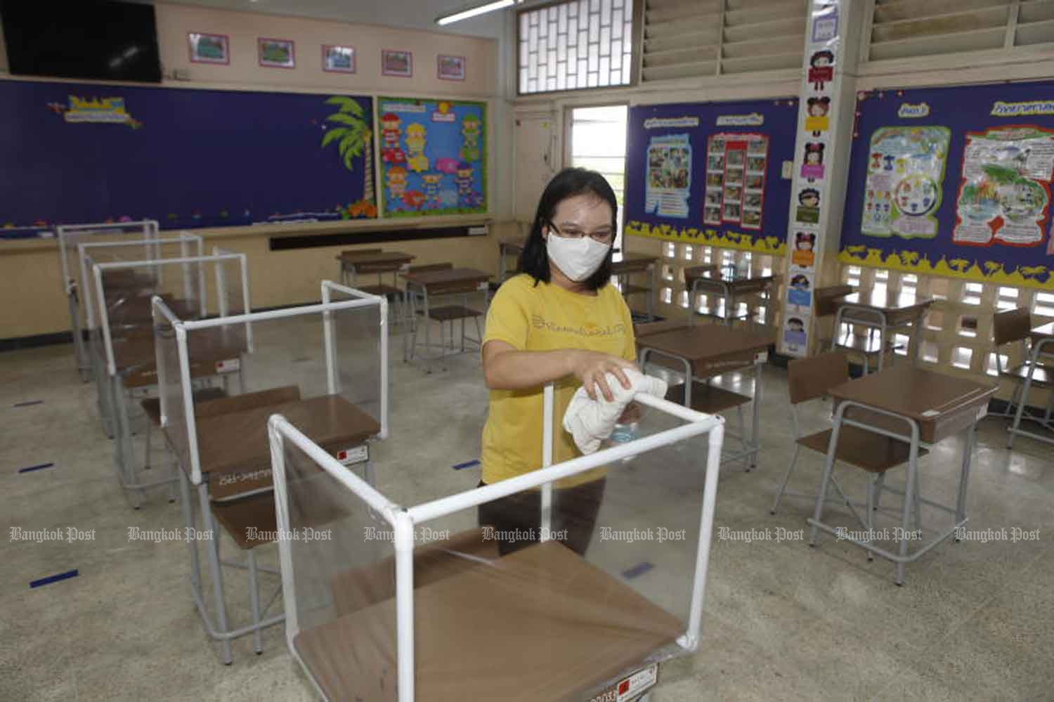 A member of staff at Or-ngern School in Bangkok's Sai Mai district cleans student cubicles. Plastic see-through partitions have been installed on tables in the cafeteria to keep students distanced from one another. (Photo: Nutthawat Wicheanbut)