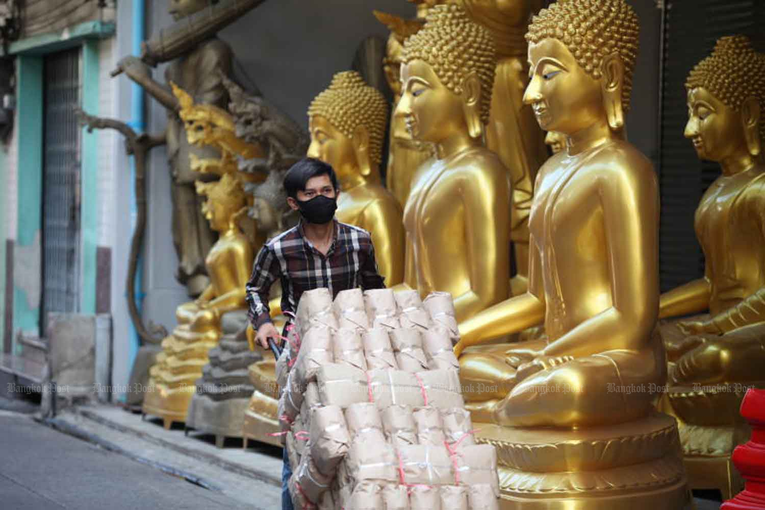 A worker wearing a face mask make a delivery in Phra Nakhon district of Bangkok on Thursday, when 17 new Covid-19 cases were reported among returnees from the Mideast. (Photo: Apichart Jinakul)