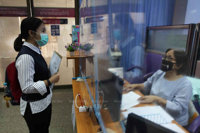 A job seeker, left, files her application at the Employment Department in Bangkok in April. Arnun Chonmahatrakool