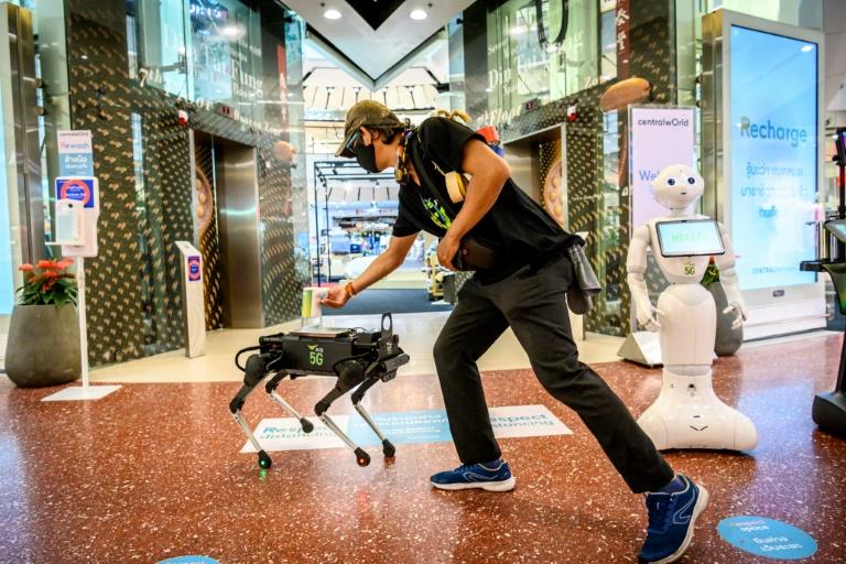 A K9 robot distributes hand sanitiser to a visitor at a shopping mall in Bangkok. (AFP photo)