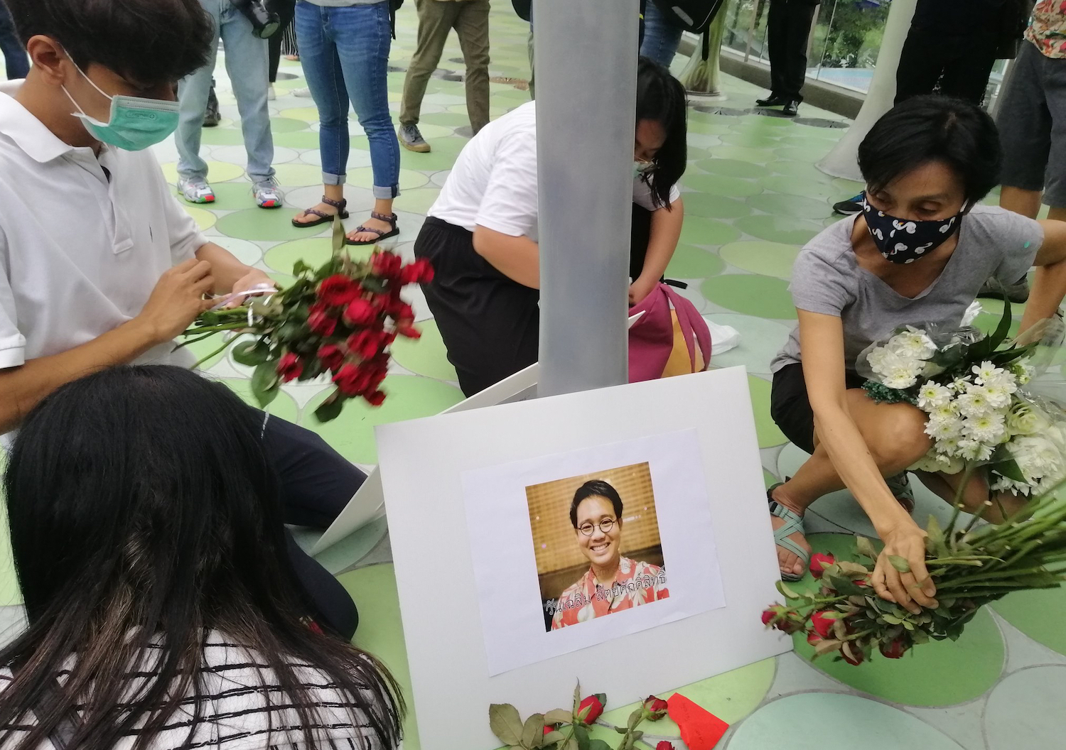 People lay flowers in front of a picture of missing activist Wanchalearm Satsaksit on the skywalk at the Pathumwan intersection on Friday. (Photo from @TLHR2014 Twitter account)